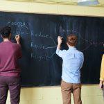 men wriiting on blackboard with chalks